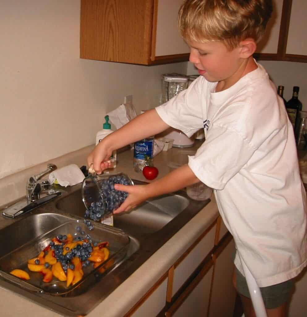 My son, Ben, helping me make Blueberry Peach Cobbler years ago